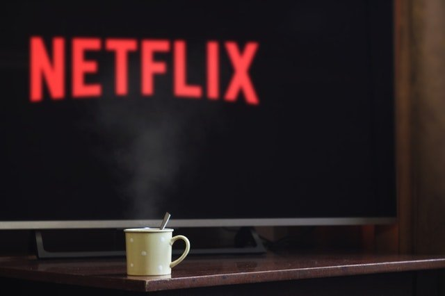 Cup near flat screen television turned onto Netflix | Photo: Pexels