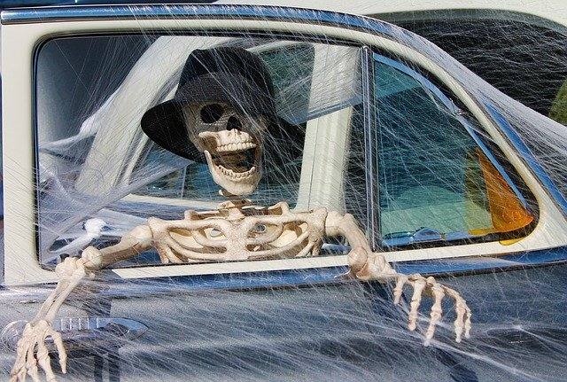 Skeleton sits open-mouthed in a web-covered car wearing a black hat | Photo: Pixabay