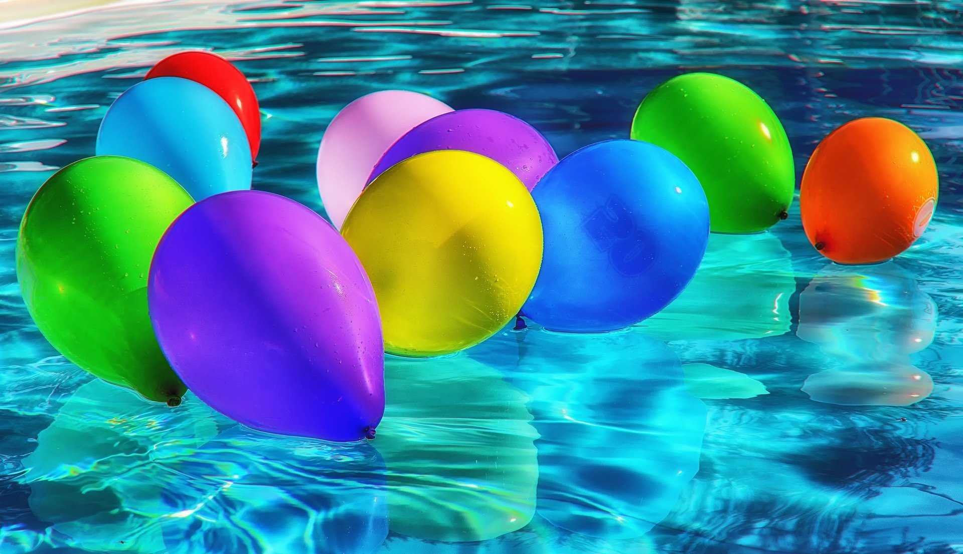 Balloons festively floating in a swimming pool. | Source: Pixabay.