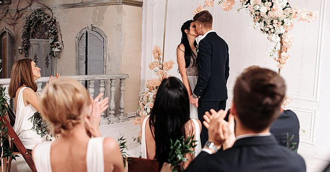 A bride and groom kissing. │Source: Shutterstock