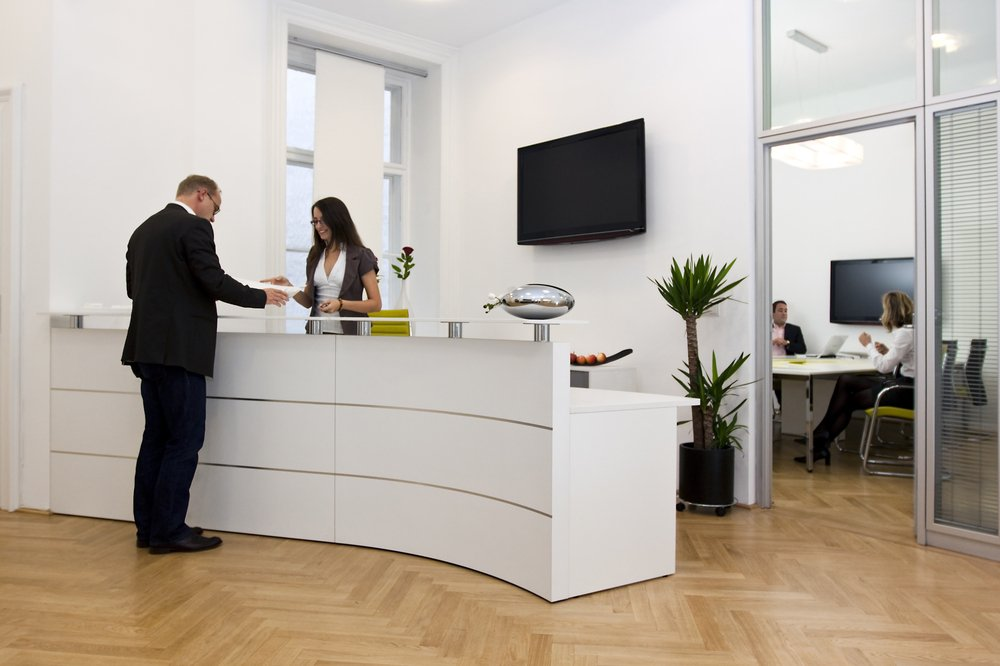 A photo of a man at the front desk writing. | Photo: Shutterstock