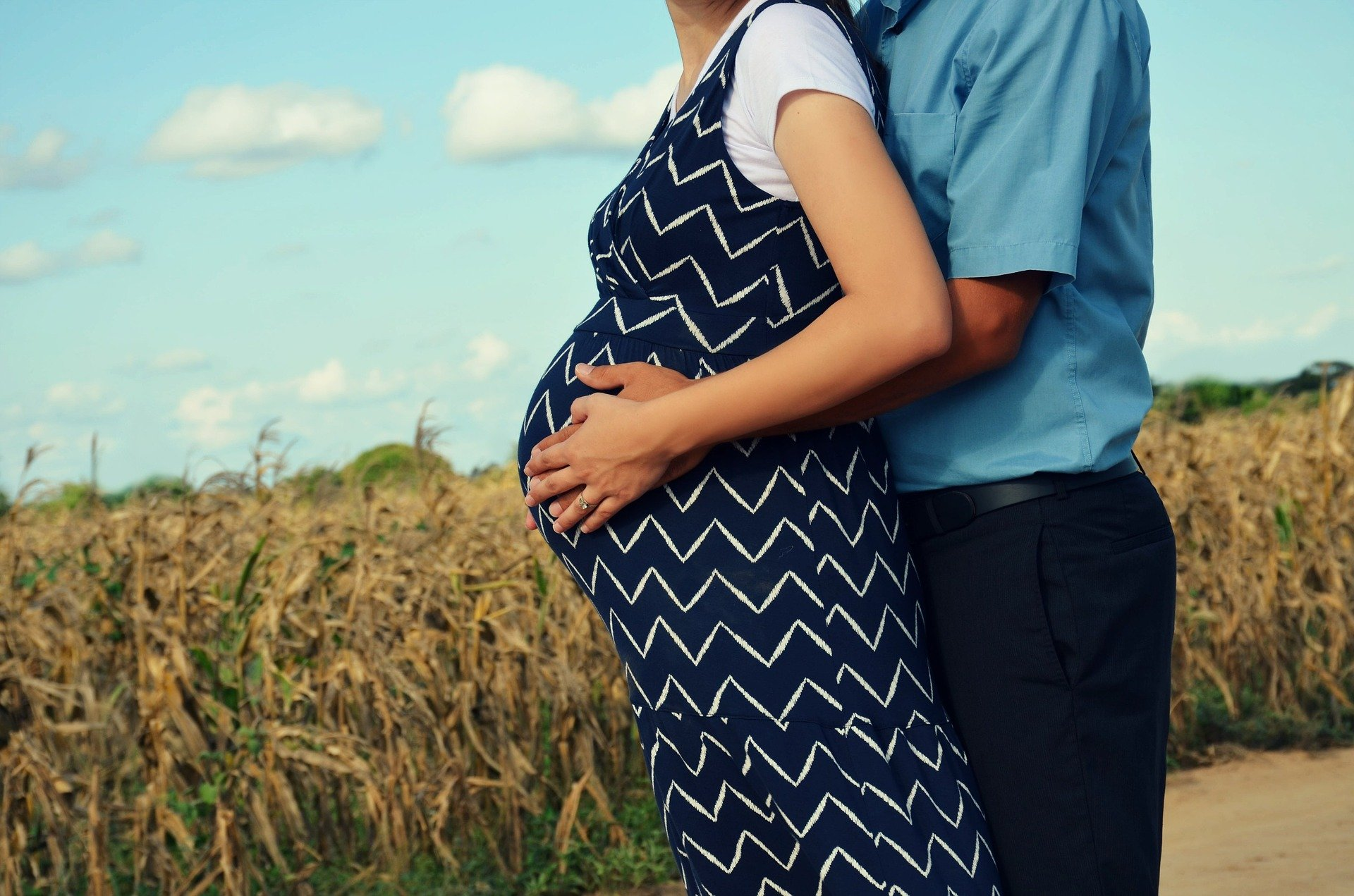 A pregnant couple standing outdoors.   Source: Pixabay.