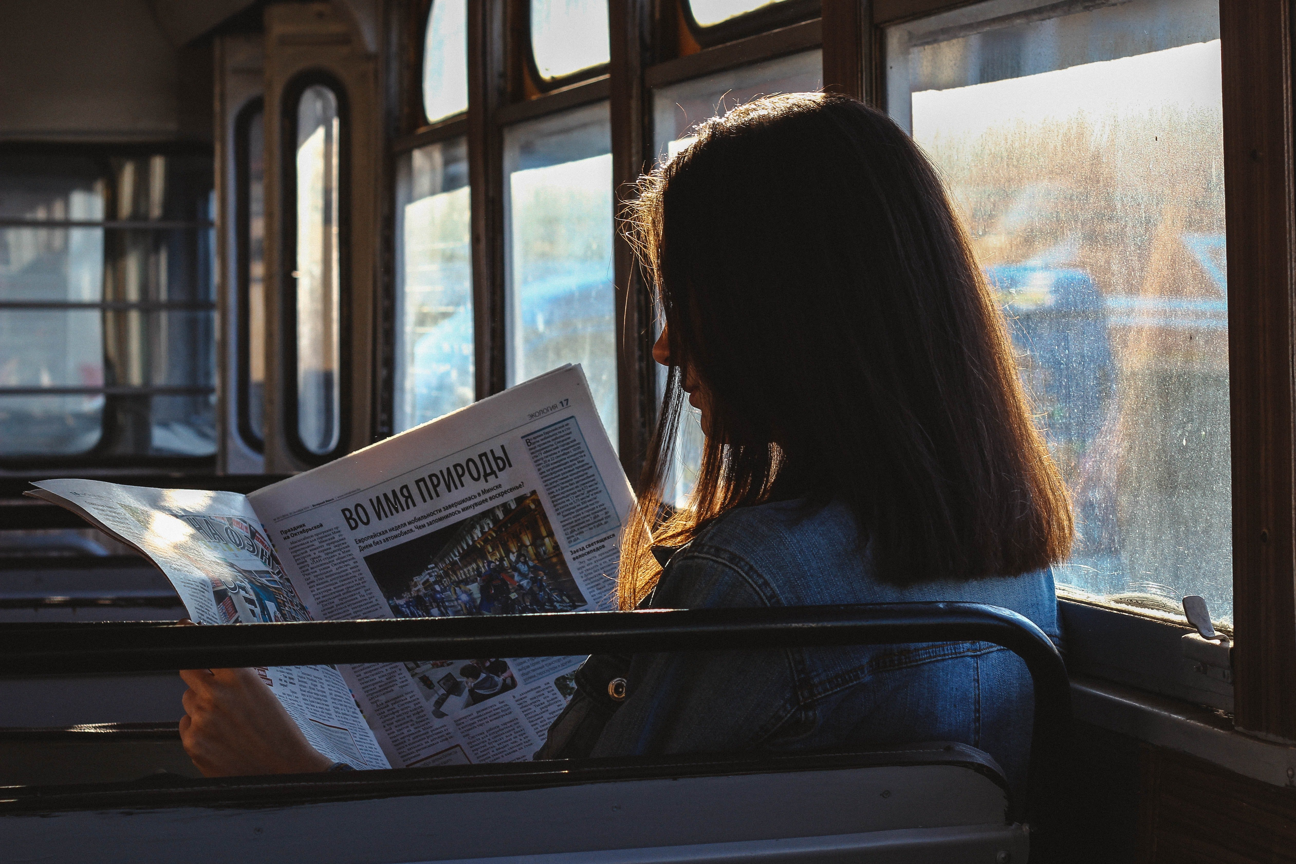 A woman reading a newspaper inside a bus | Photo: Pexels