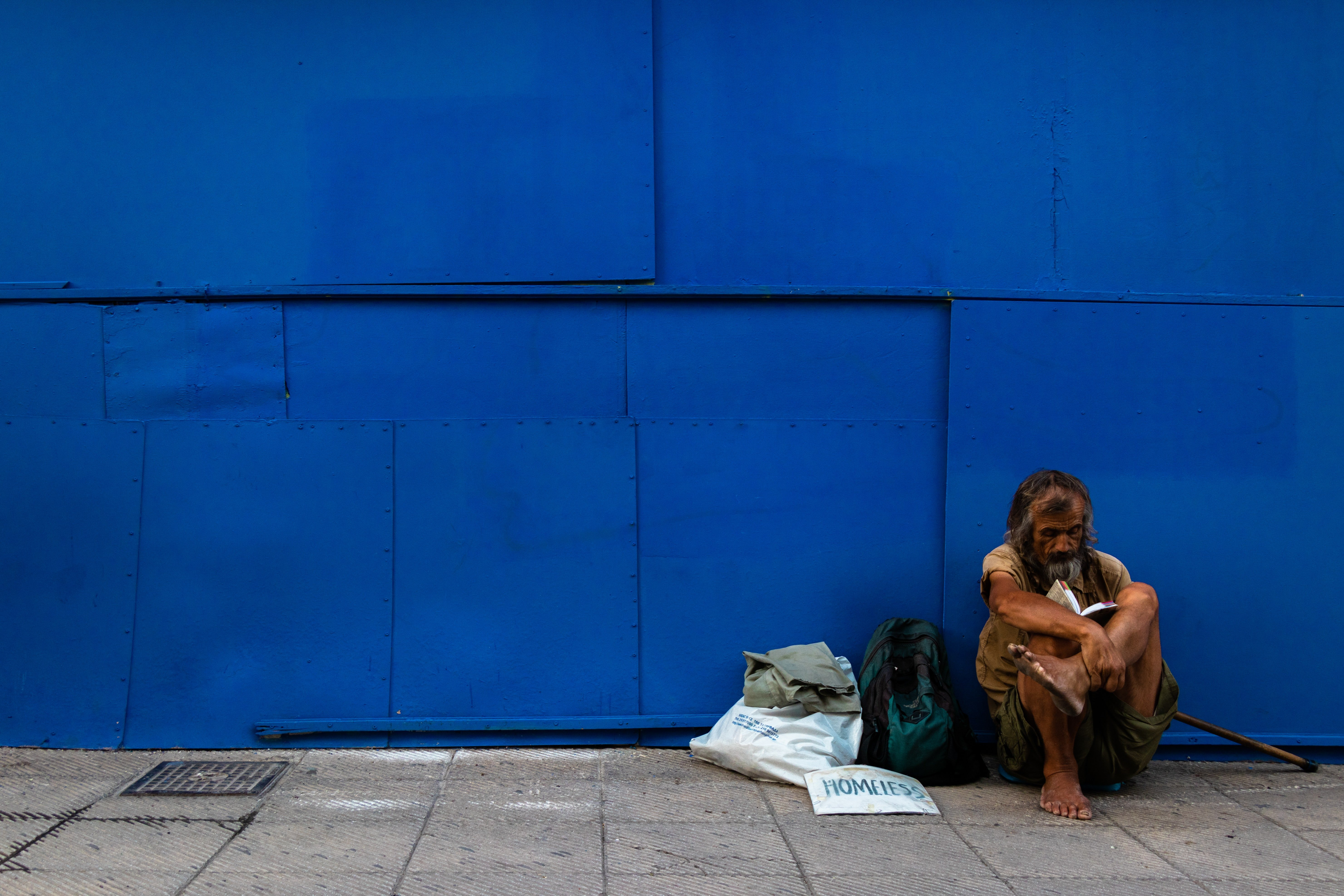 Man sitting against a blue wall sitting next to a couple of bags   Source: Unsplash / Jonathan Kho