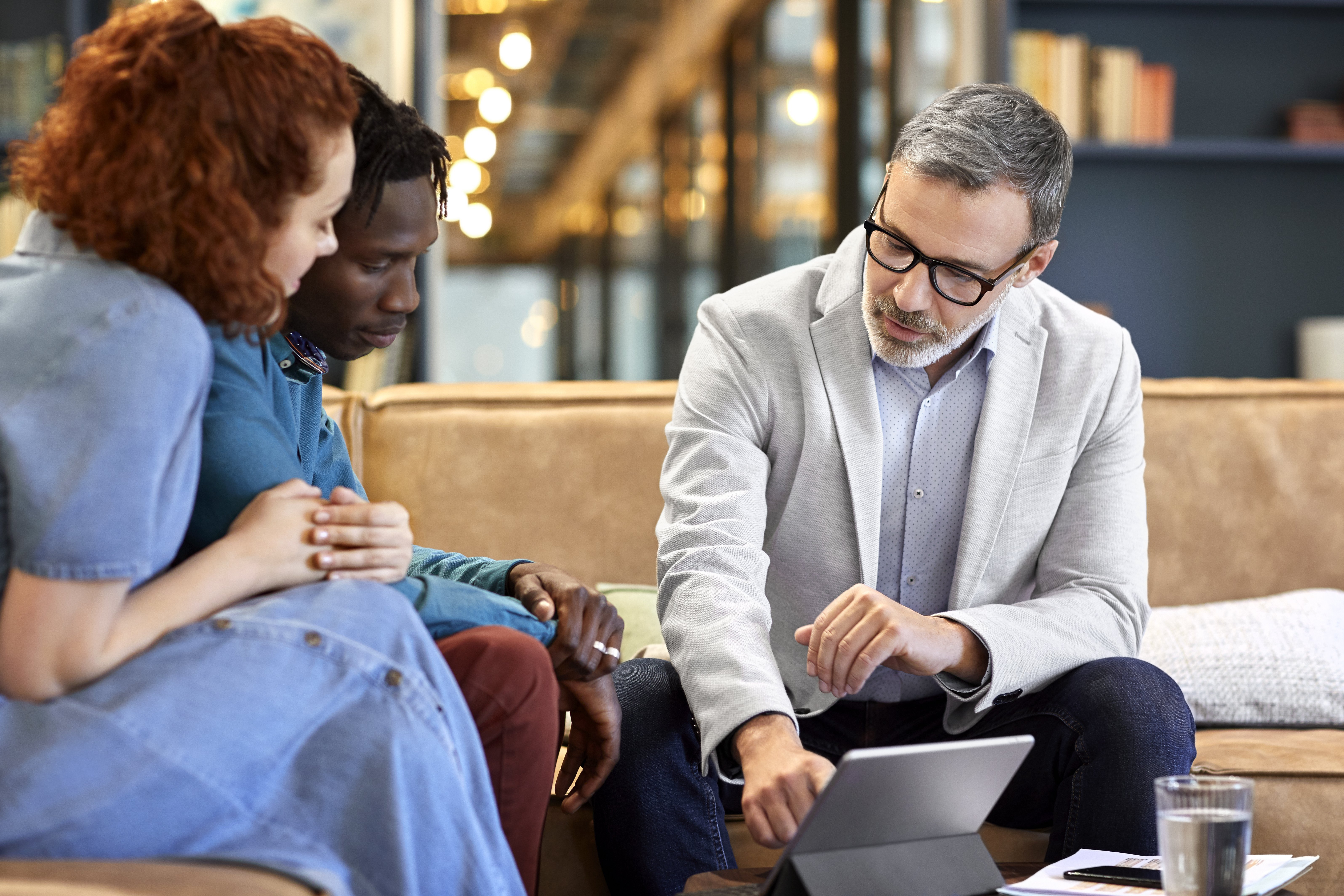 Mature financial advisor planning with young multi-ethnic couple at office. Businessman is discussing over digital tablet with clients at workplace. They are sitting in meeting.|Photo: Getty Images