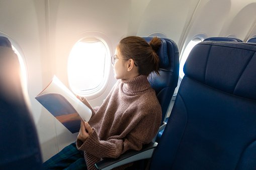 Photo of a young woman looking through the window while sitting with book in airplane | Photo: Getty Images