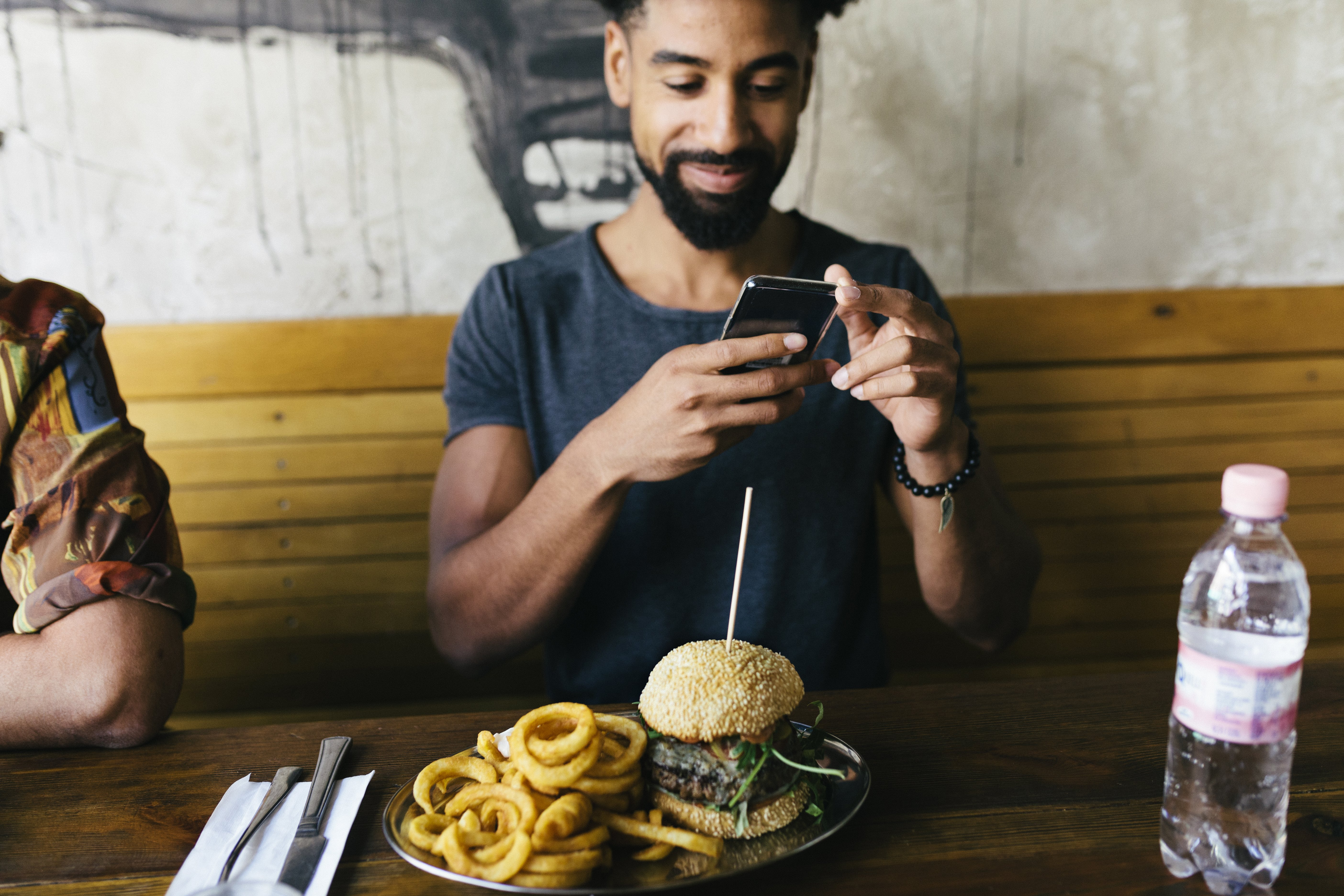A man using his smartphone, taking photos of his burger before eating it at a trendy restaurant. | Photo: Getty Images