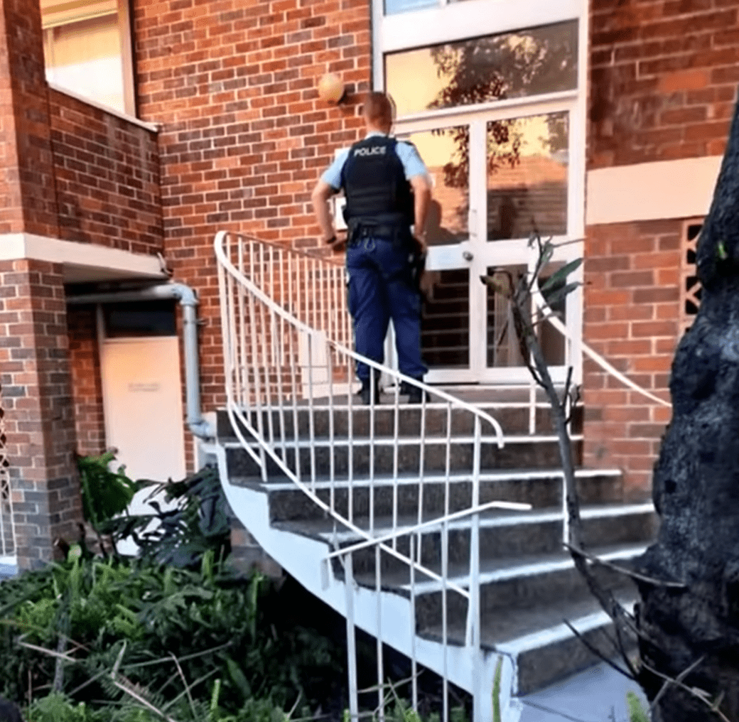 Police officer standing in front of a door.   Source: youtube.com/7NEWS Australia