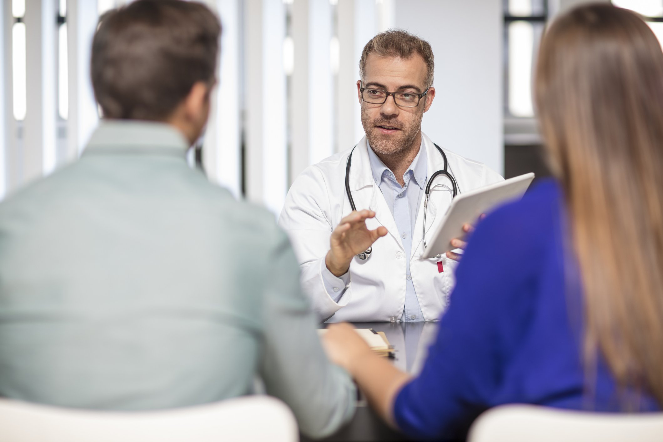 Doctor talking to couple in medical practice | Photo: Getty Images