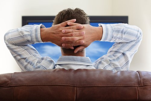 A man relaxing watching television. | Source: Shutterstock.
