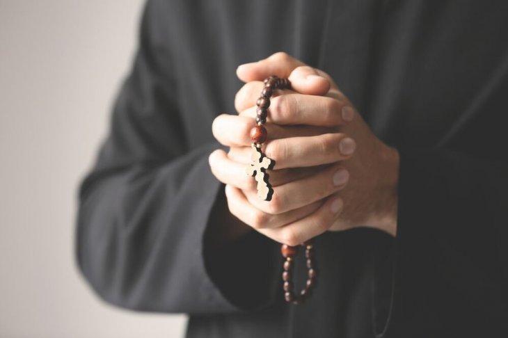 Sacerdote sosteniendo un rosario entre sus puños cerrados.   Imagen: Shutterstock