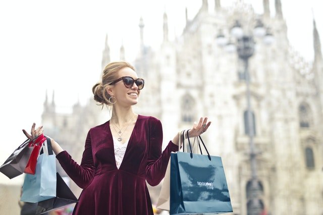 Woman with sunglasses hold a few shopping bags in hand | Photo: Pexels