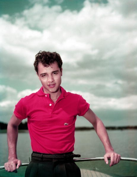 Sal Mineo poses in a red Lacoste polo shirt aboard a boat, 1950s. | Source: Getty Images.