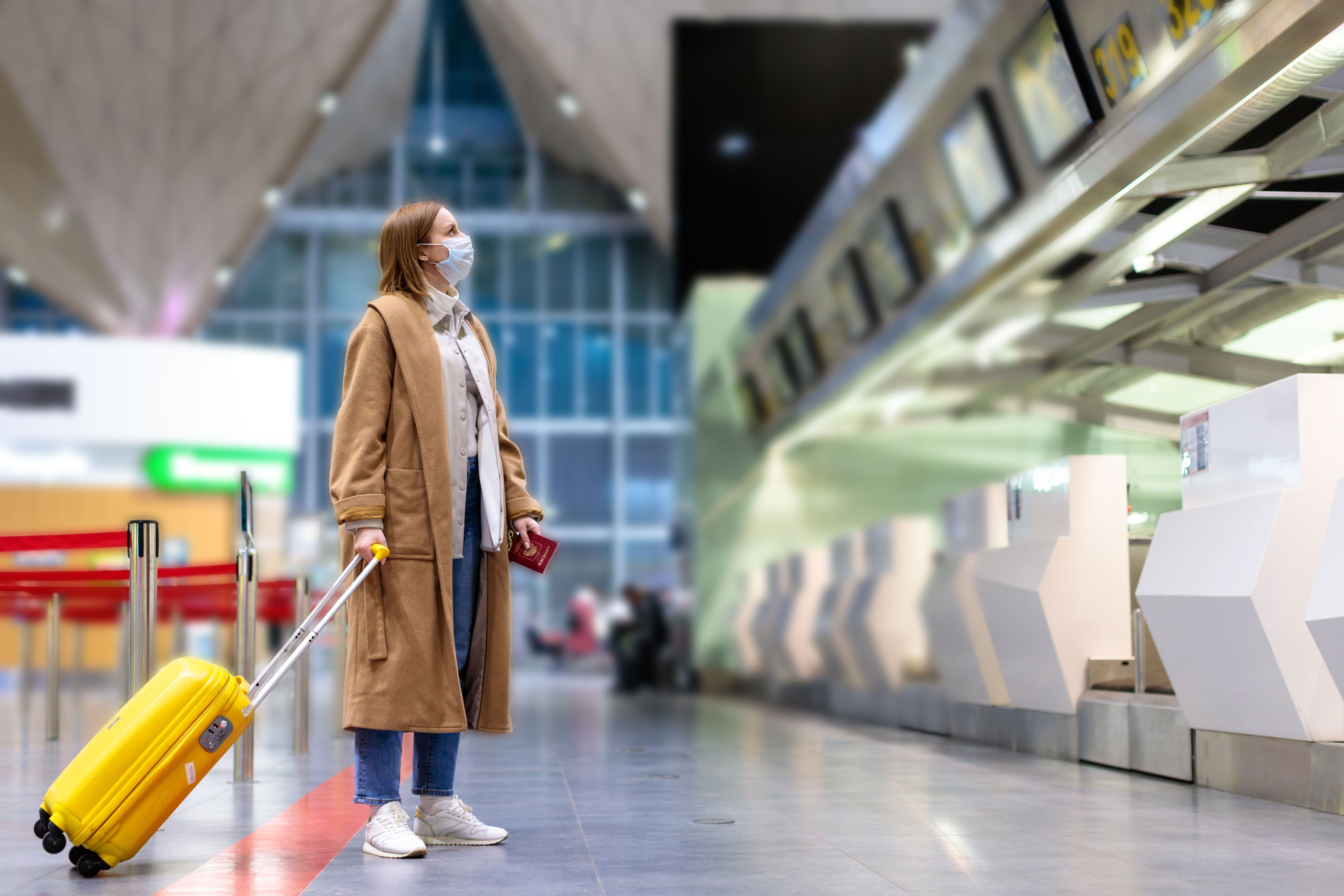 Woman with luggage standing at in front of a check-in counter at the airport terminal during the Covid-19 pandemic   Photo: Shutterstock
