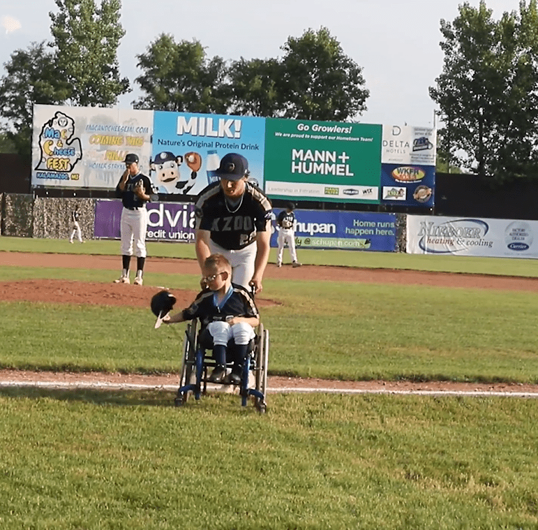 A baseball player for the Kalamazoo Growlers pushing Brenden Lowery in his wheelchair off a football field. │Source: Facebook/kzoogrowlers