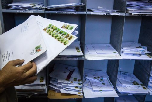 A postman sorting letters. | Source: Shutterstock.