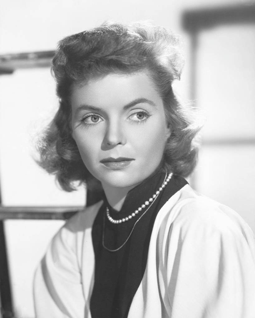 Dorothy McGuire (1916-2001) wearing a white cardigan over a black high-neck blouse with a pearl necklace, in a studio portrait, circa 1950.   Photo: Getty Images