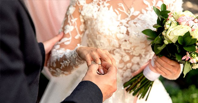 A groom putting the wedding ring on his bride.   Source: Shutterstock