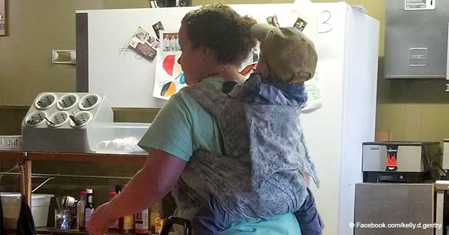 Here's the story behind the viral photo of busy waitress working with toddler strapped to her back