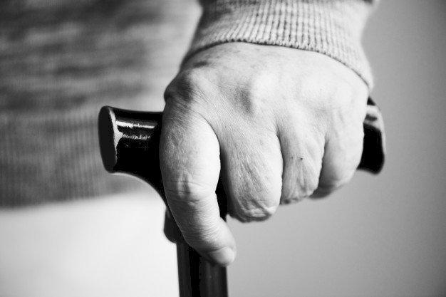 La main d'une personne âgée tenant une canne   Source : Freepik