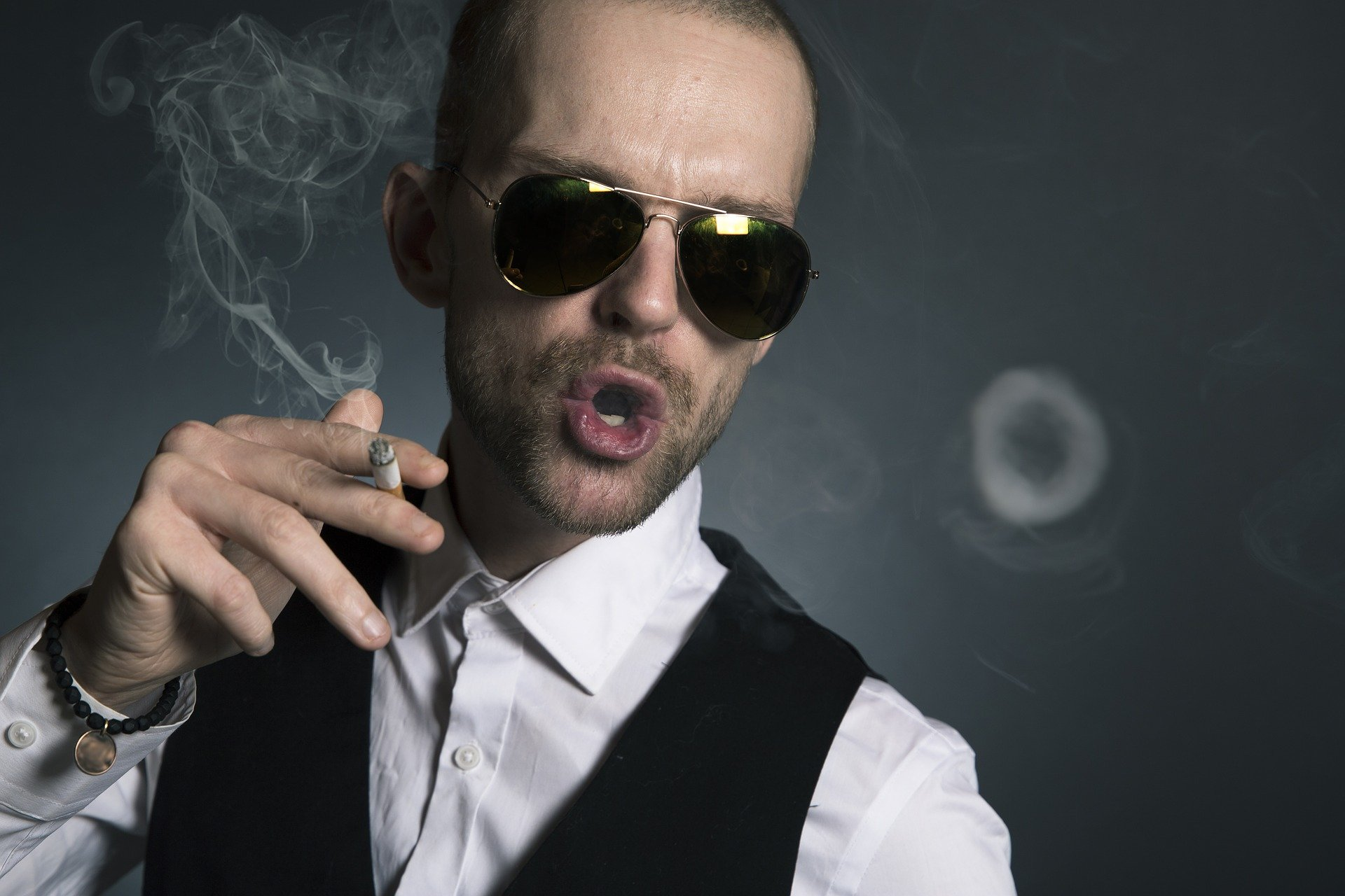 An arrogant rich man wearing sunglasses while blowing out cigarette smoke   Photo: Pixabay/Sammy-Williams