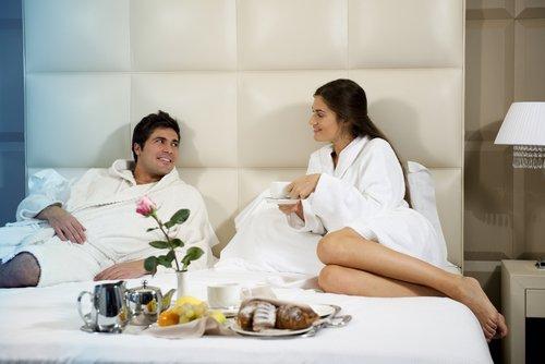 Un couple détendu au lit dans une chambre d'hôtel | Photo : Shutterstock