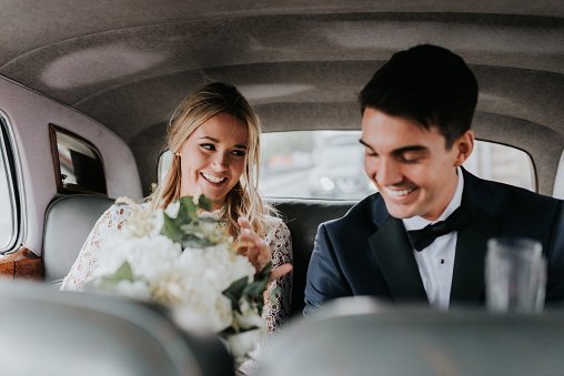 Bride and bridegroom in backseat of car | Photo: Getty Images