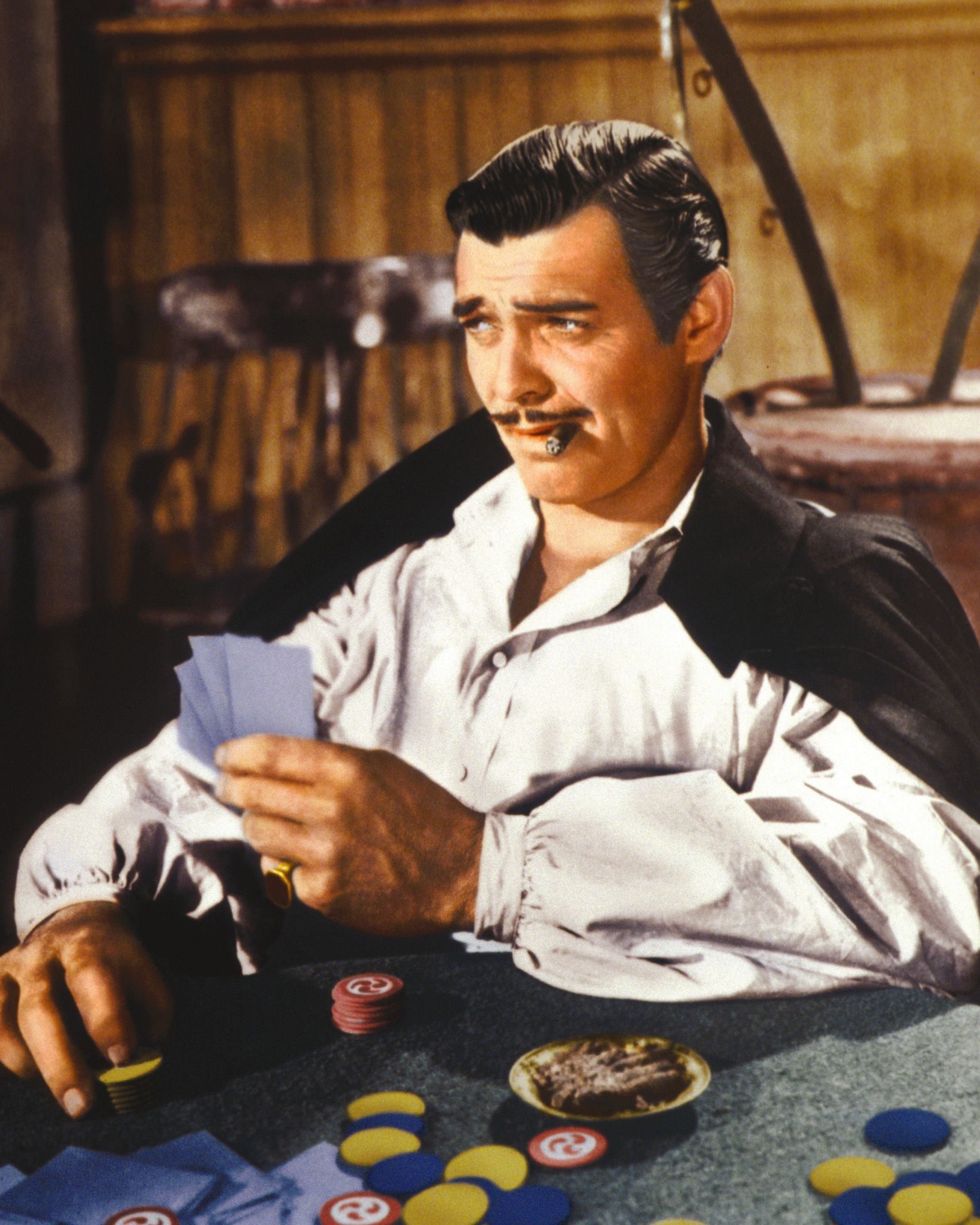 """Clark Gable playing cards and smoking a cigar in a publicity still issued for the film """"Gone With The Wind,"""" 1939. 