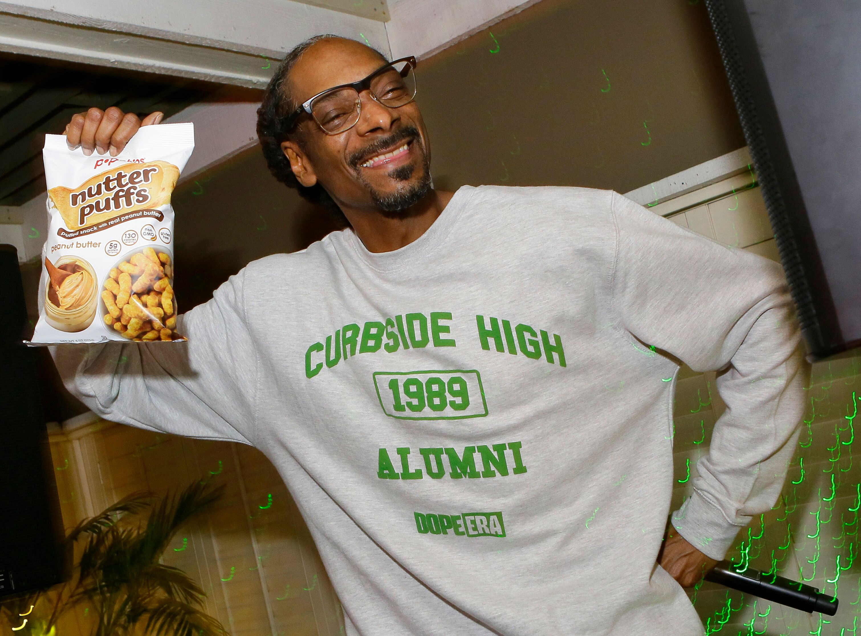 Rapper Snoop Dogg wearing a mock high school sweatshirt | Source: Getty Images