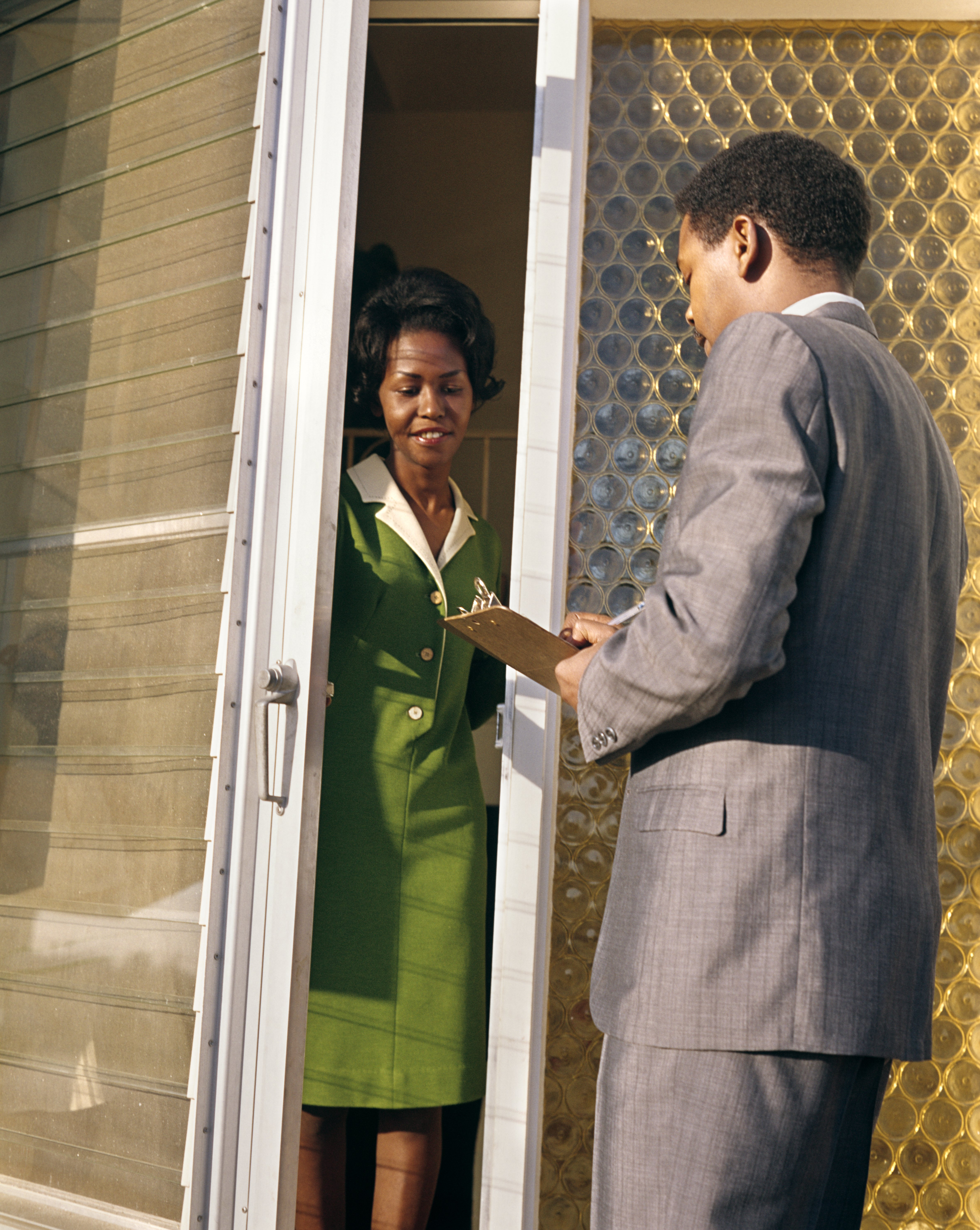 1960s 1970s AFRICAN AMERICAN SALESMAN MAN HOLD CLIPBOARD TALK TO WOMAN FRONT DOOR | PHOTO: GETTY IMAGES