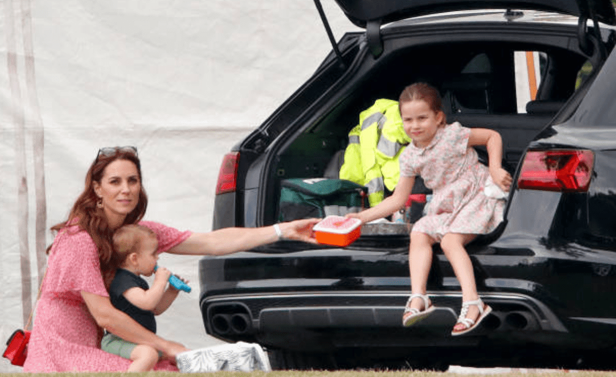 Kate Middleton holds Prince Louis and passes a lunch box to Princess Charlotte as they sit by their car at the King Power Royal Charity Polo Match, on July 10, 2019, England   Source: Getty Images