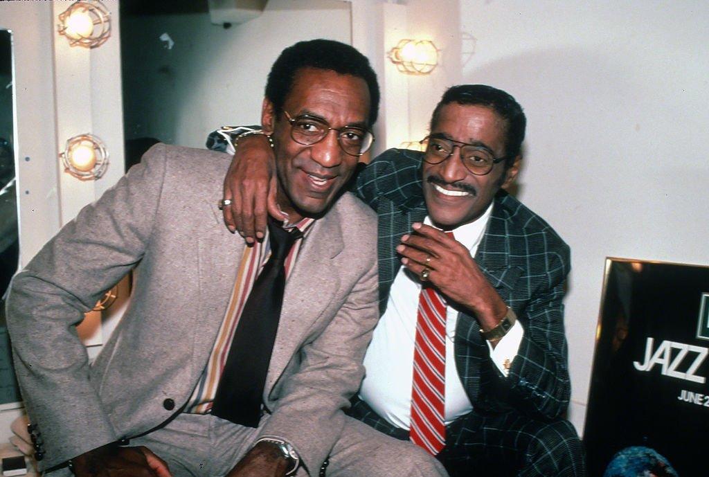 Sammy Davis Jr. embrace Bill Cosby while sitting backstage in front of a mirror on January 1, 1971, New York City | Source: Images Press/IMAGES/Getty Images