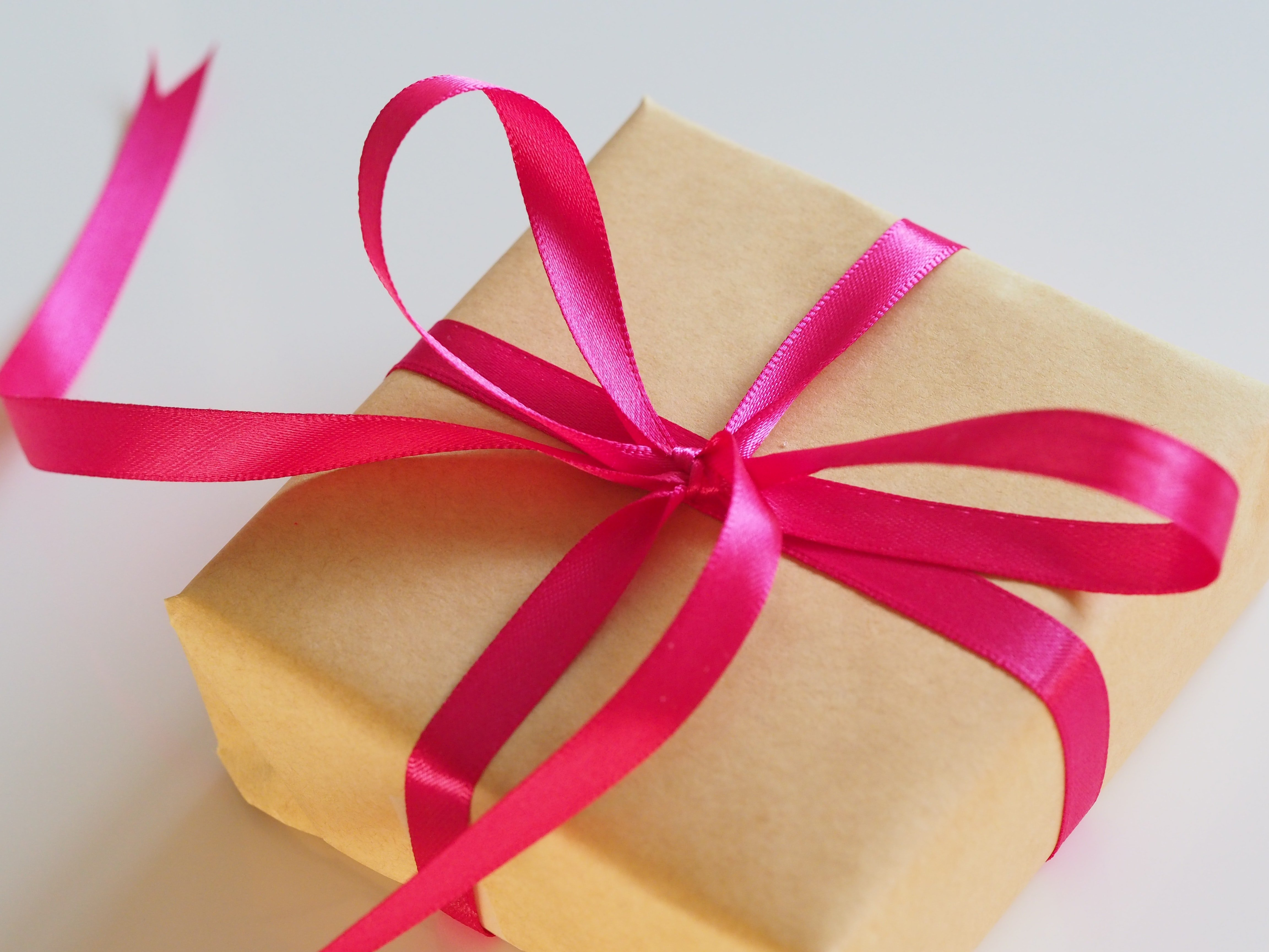 Brown gift box with a red ribbon | Source: Unplash