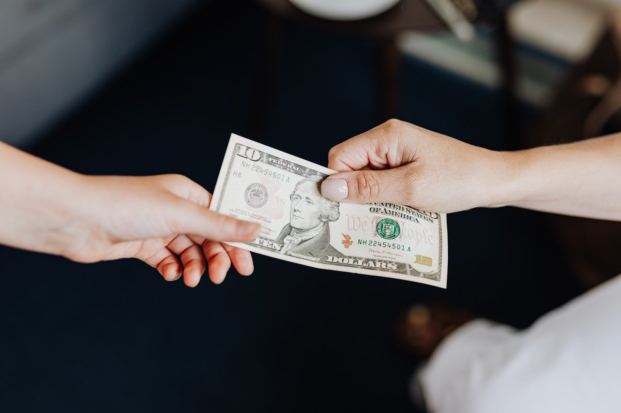 Hands exchanging a $10 bill | Photo: Pexels