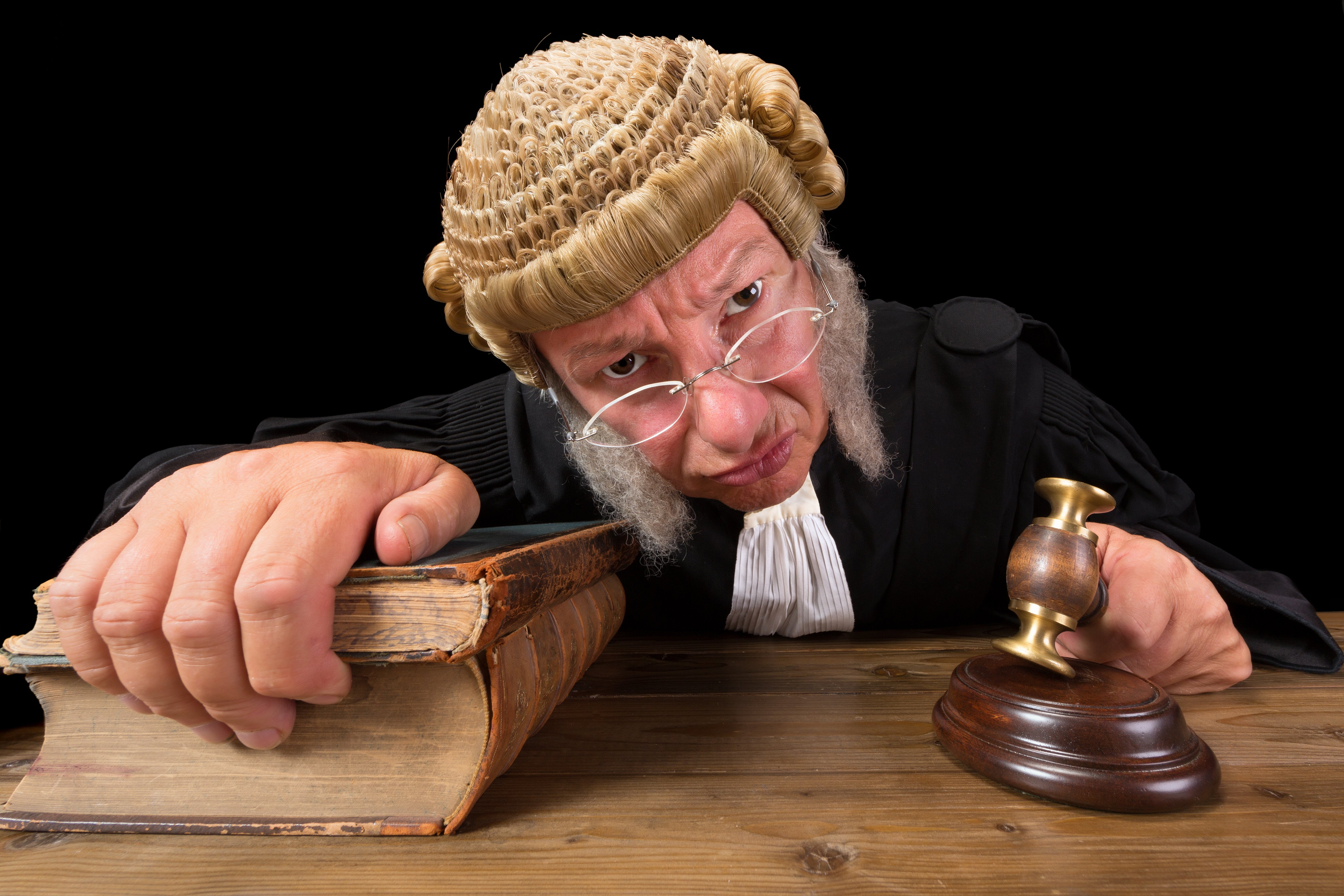 Angry judge with a hammer and a wig, holding legal tomes. Image credit: Shutterstock
