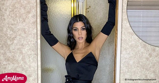 Kourtney Kardashian tempts fans in a seductive black mini dress, raising her arms in racy gloves