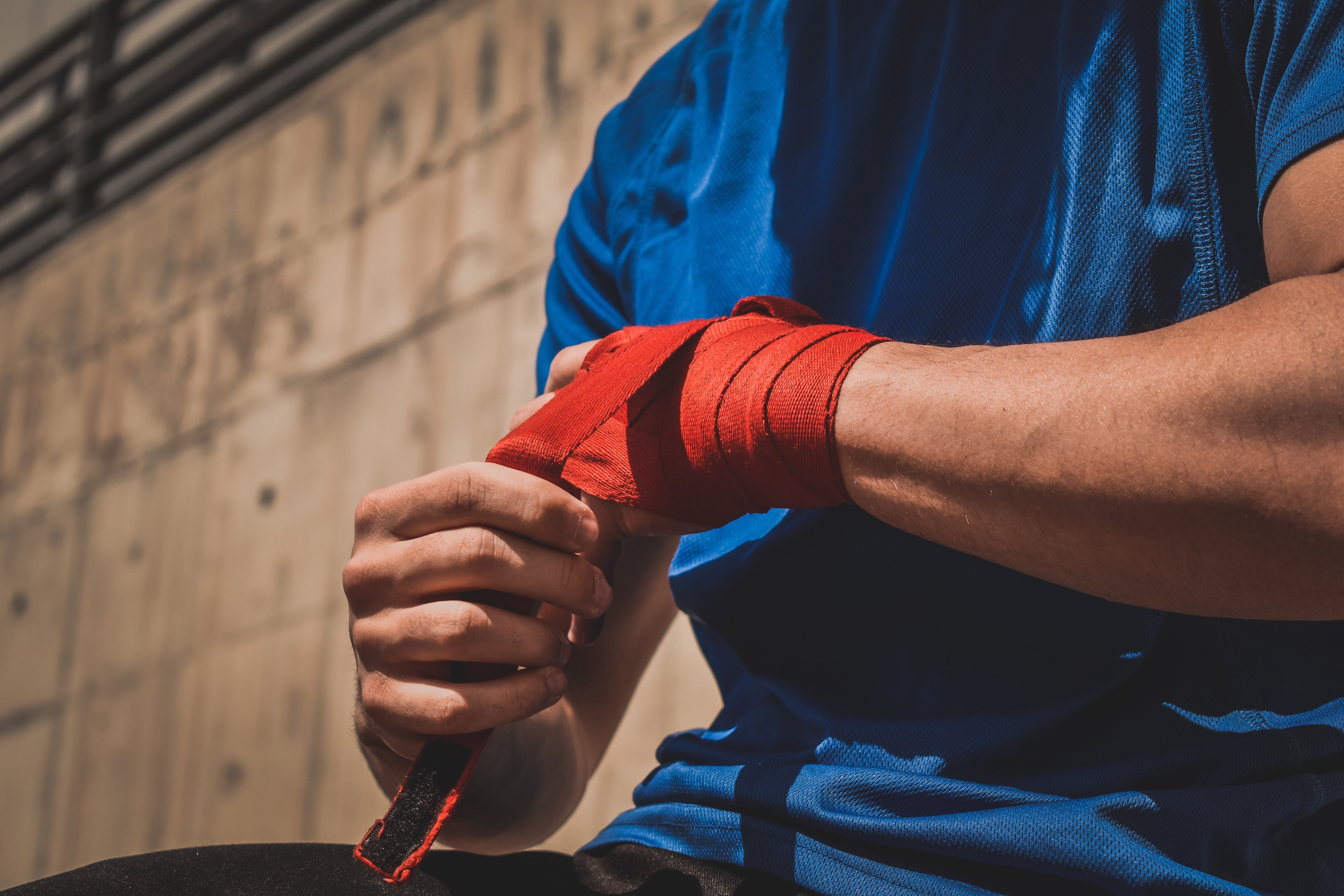 Man wearing a blue T-shirt and fixing his boxing hand wrap  | Source: Unsplash / Payam Tahery