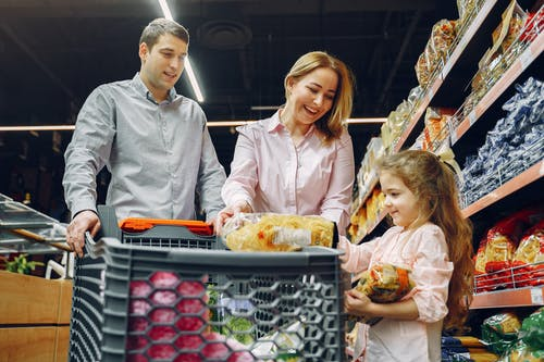 Man, woman and child in a supermarket | Source: Pexels