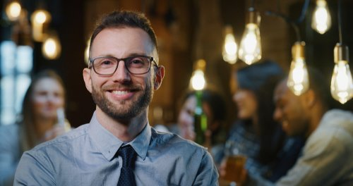Man at a bar smiling broadly at the bartender.   Source: Shutterstock.