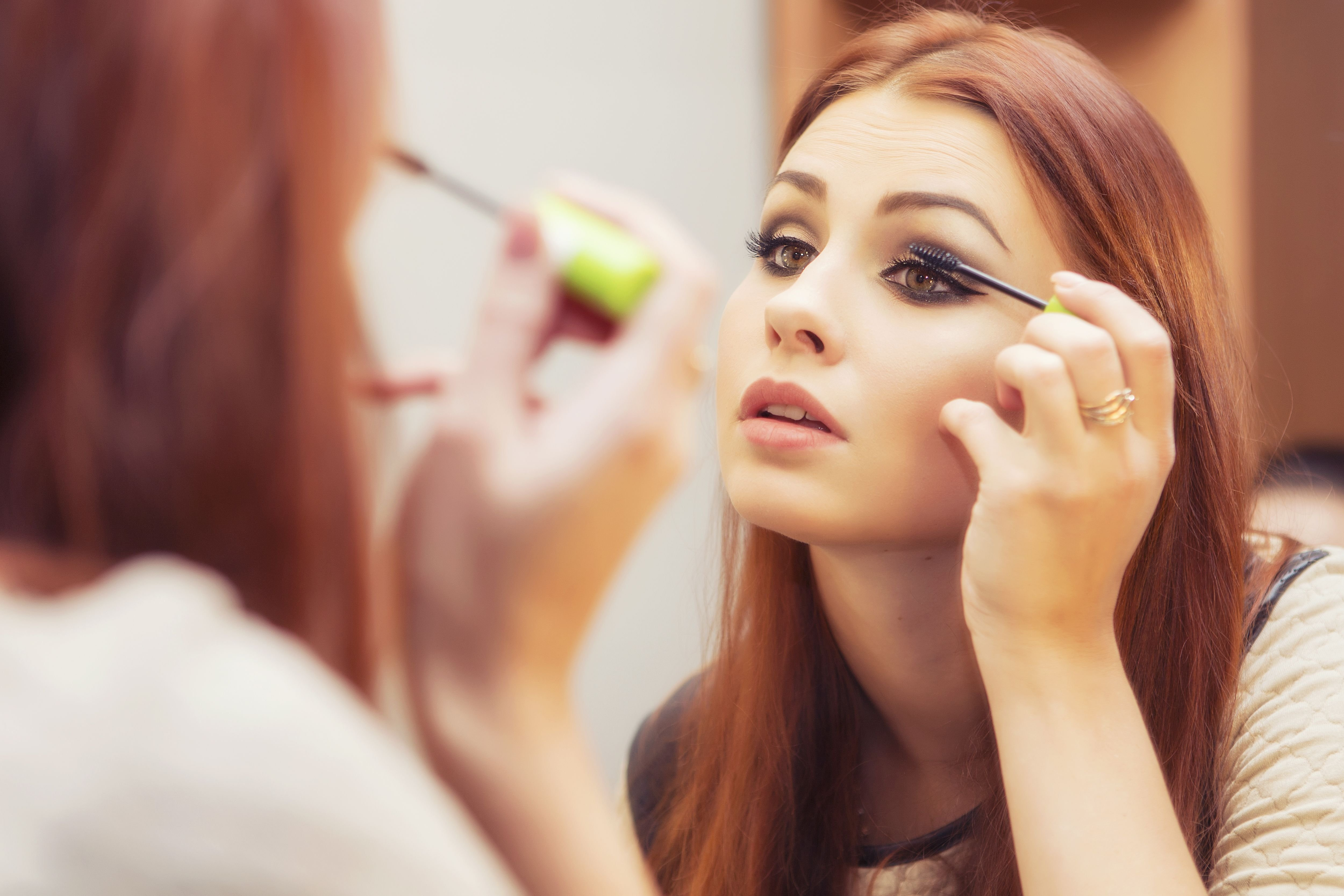 A woman applying make up in front of a mirror. | Source: Shutterstock