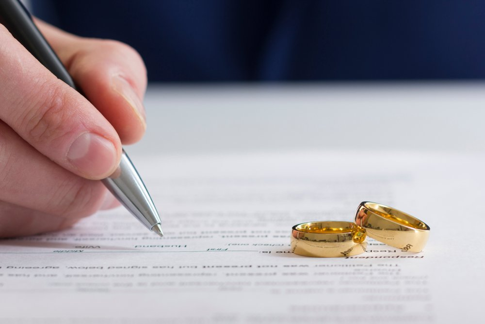 A portrait of the hands of wife, husband signing decree of divorce. | Photo: Shutterstock