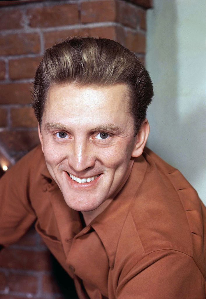 Kirk Douglas smiles for the camera in front of a brick wall backdrop, on January 1, 1960 | Source: Sunset Boulevard/Corbis via Getty Images