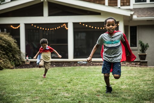 Photo of young boys in capes playing in backyard | Photo: Getty Images