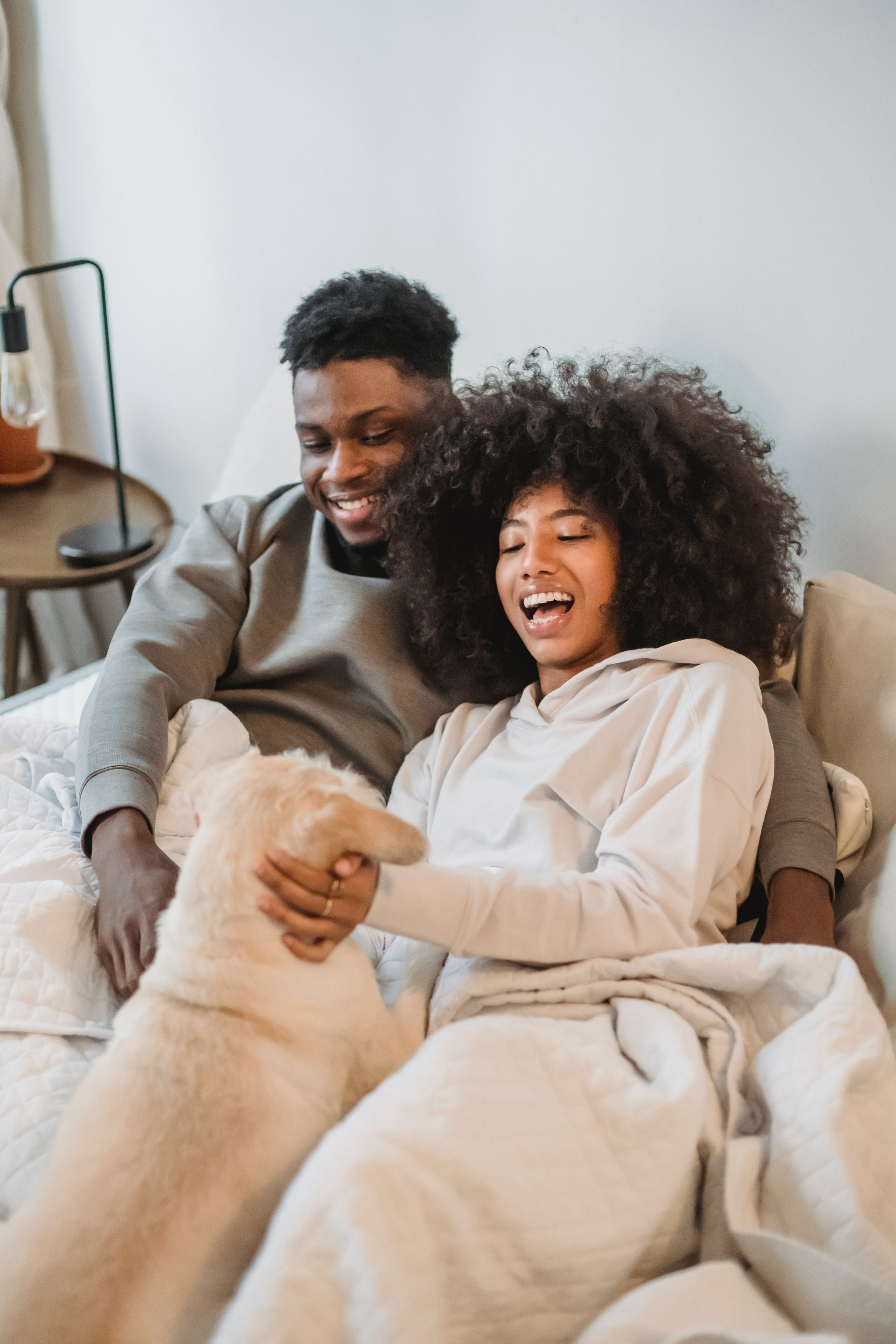 Pictured - A young couple snuggling up with their dog on the bed. | Source: Pexels