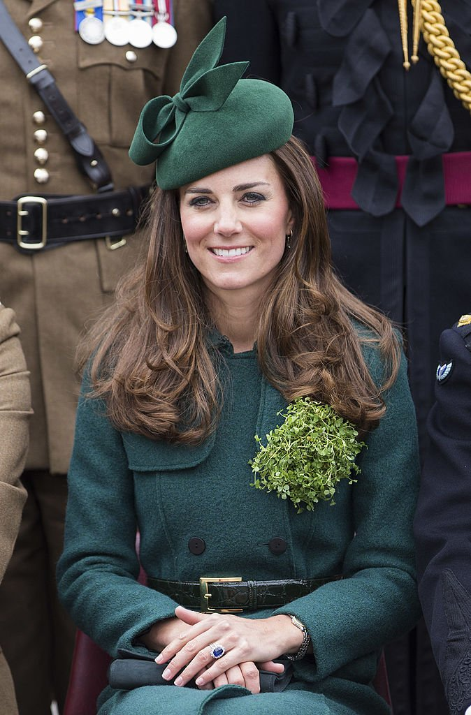 Kate Middleton, Duchess of Cambridge is all smiles while sitting down wearing an all-green ensemble with a matching headpiece | Photo: Getty Images