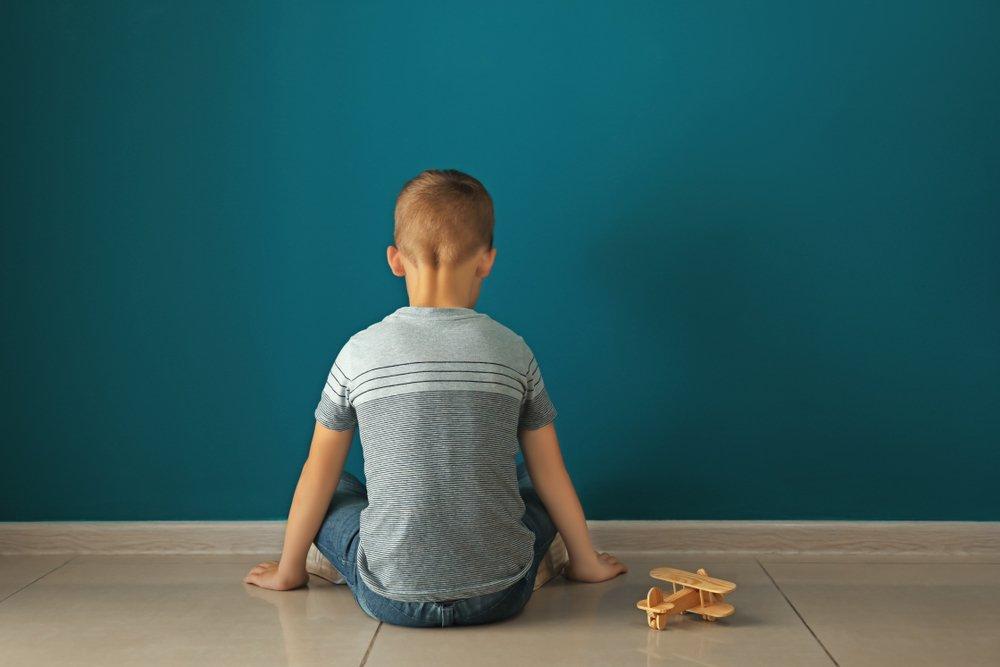 Autism Concept: Little boy sitting near dark wall in empty room | Source: Shutterstock