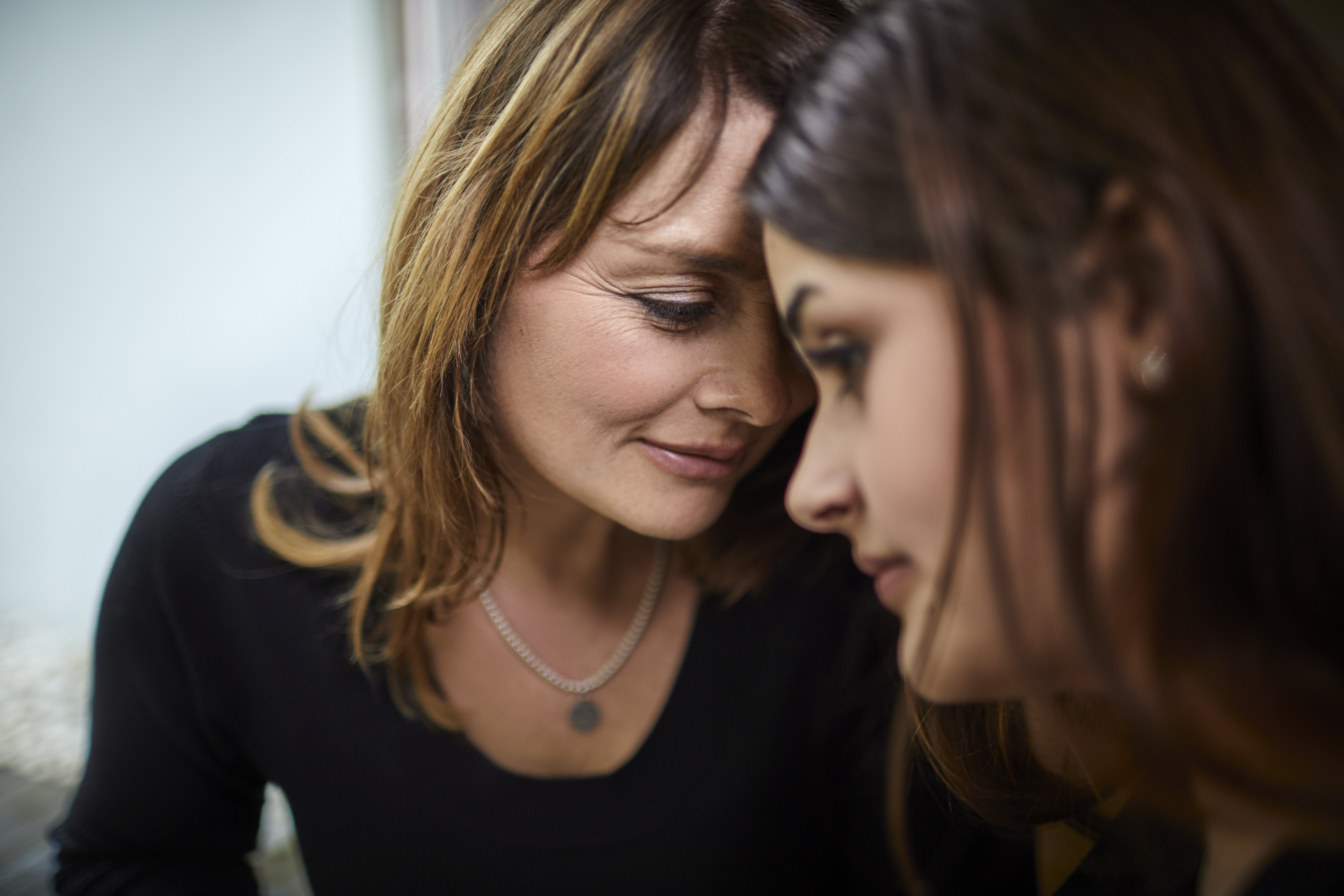 Portrait of mature mother with teenage daughter close together  Photo: Getty Images