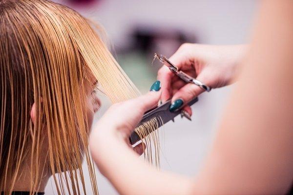 Mujer cortándose el cabello. Fuente: Shutterstock
