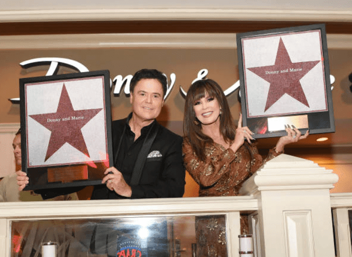 Donny Osmond and Marie Osmond posing as they receive their star's on the Las Vegas strip, on October 04, 2019, in Las Vegas, Nevada | Source: Denise Truscello/WireImage/ Getty  Images