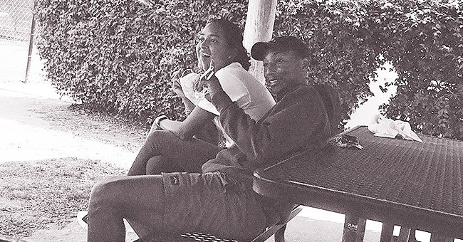Pharrell Williams & His Wife of 7 Years Smile while Chilling Together on a Bench in Rarely-Seen Pic
